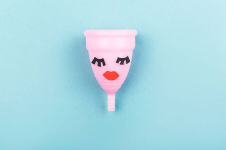 Creative menstrual cup with eyelashes and red lips on blue background. Trendy feminine sanitary product. Ñonfidence in period days. Flat lay, top view.