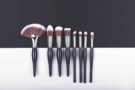Set of makeup brushes on black and grey color block background. Minimal concept. Flat lay, top view.
