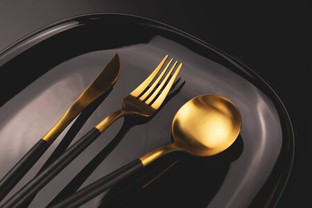 Set of stylish black and gold cutlery on the plate. Dark and moody vibes. Fashionable and luxury eating. Flat-lay, top view. Copy space for your text.