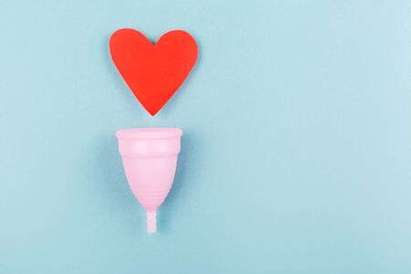Creative menstrual cup and red heart on blue background. Trendy feminine sanitary product. Ñonfidence in period days. Flat lay, top view.