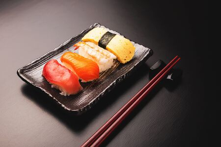 Set of tasty sushi on black background. Traditional Japanese food concept.