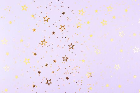 Falling golden stars confetti on purple background. Flat lay, top view. Copy space.