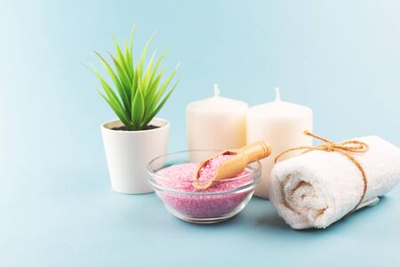 Beauty composition with pink salt and towel on blue background. Selfcare, home spa and relaxation concept. Flat lay, top view. Stock fotó