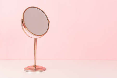 Gold mirroron pink background. Vanity table concept.