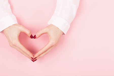 Woman hands in a heart shape on pink background.