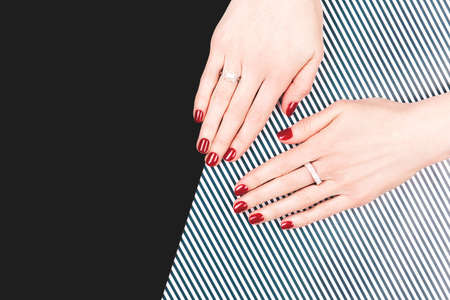 Woman hands with perfect classic manicure with red polish.