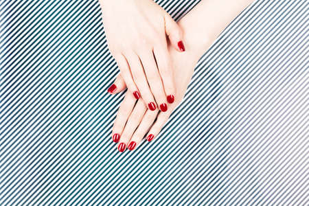 Two woman hands with perfect manicure on black and white striped background.