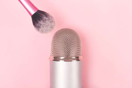 A makeup brush and a professional microphone on pink backround. Making ASMR sounds.