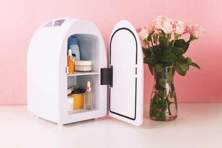 Mini fridge on pink background. Minimal composition.