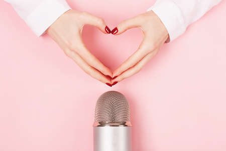 Woman hands in a heart shape and a microphone on pink background. Stok Fotoğraf