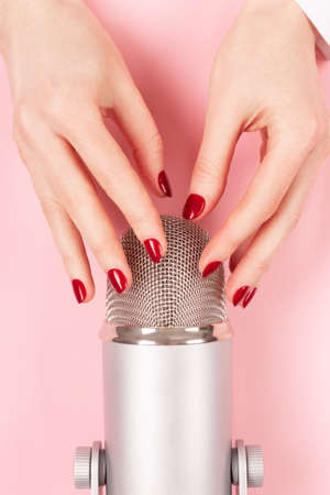 Woman hand with perfect manicure near the microphone. Making ASMR sounds. Stok Fotoğraf