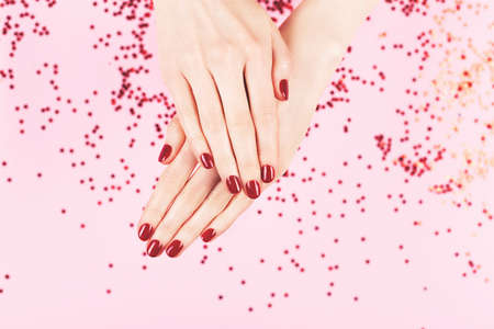 Two woman hands and falling confetti on pink background.