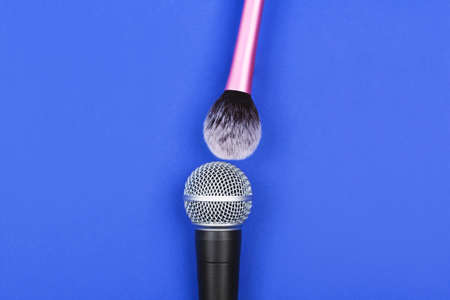 A microphone with a makeup brush on vivid blue background. Stok Fotoğraf