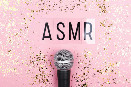 A microphone and letters ASMR on pink background. Minimal compostion.