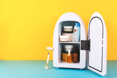 Mini fridge on yellow and blue background. Minimal composition.