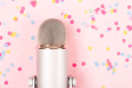 A microphone on pink background decorated with confetti. Minimal compostion.