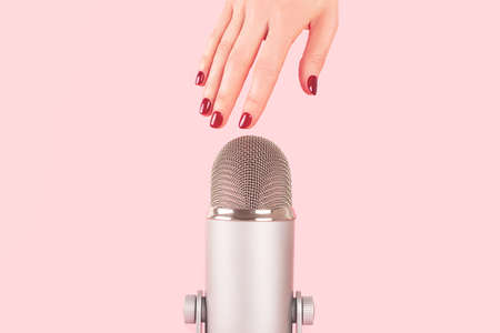 Woman hand with perfect manicure near the microphone. Making ASMR sounds. 版權商用圖片
