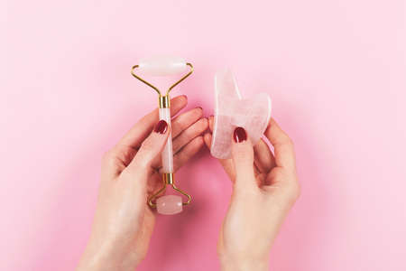 Jade roller and gua sha tool in woman hands. 版權商用圖片
