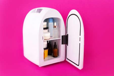 Mini fridge on vivid magenta background. Minimal composition.