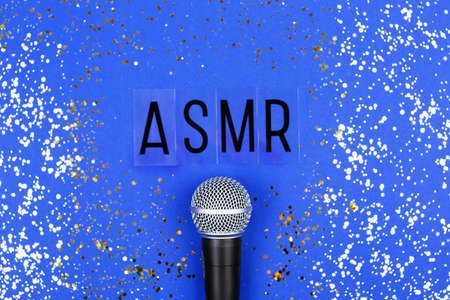 A microphone and letters ASMR on blue background. Minimal compostion.