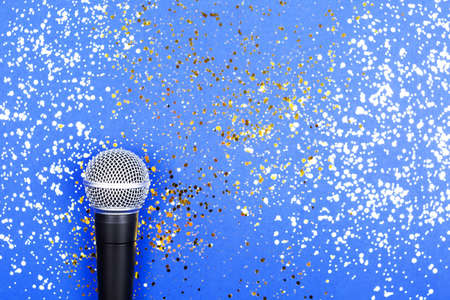 A microphone on blue background decorated with confetti. Minimal compostion.