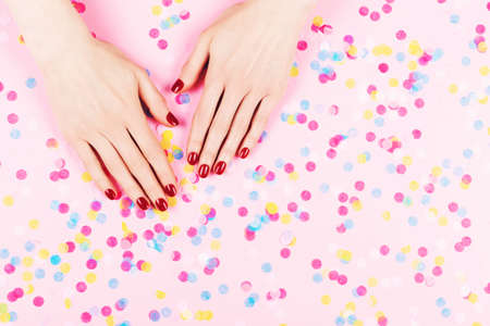 Two woman hands with perfect manicure and falling colorful confetti on pink background.