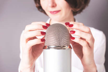 Unrecognizable girl and the microphone. Podcast, ASMR, livestream, video recording concept.