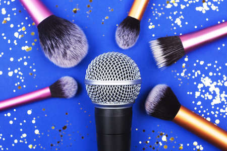A microphone with many brushes decorated with confetti.