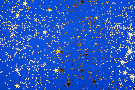 Falling gold color confetti on vivid blue background. Stok Fotoğraf