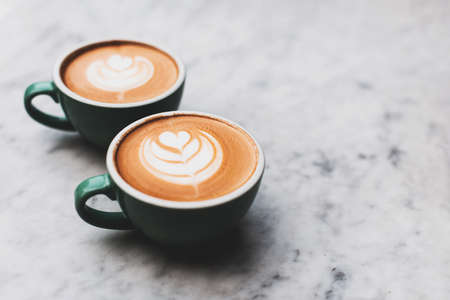 Two beautiful cups of cappuccino on the table.