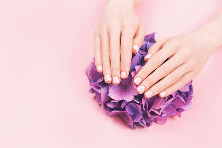 Woman hands with perfect pastel pink manicure.
