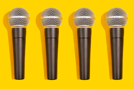 Pattern made with microphones on the yellow background. 版權商用圖片