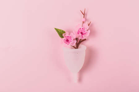 A menstrual cup on the pink background. Decorated with a flower. Zero waste period concept.