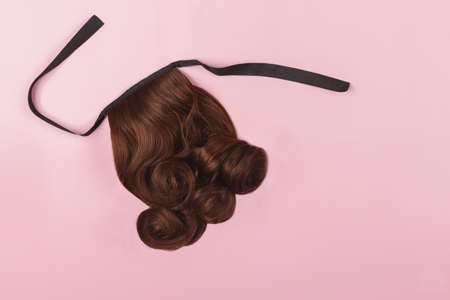 A brown hairpiece on the pink background. Flat-lay. 版權商用圖片