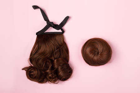 A brown hairpieces on the pink background. Flat-lay. 版權商用圖片