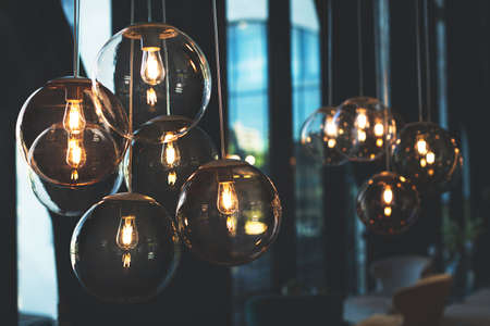 Cozy light bulbs in dark and moody cafe.