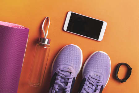 Home workout concept. Sneakers, water bottle and smartphone.