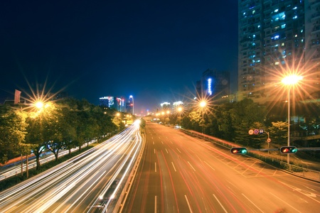 road with car traffic at night and blurry lights showing speed and motion photo