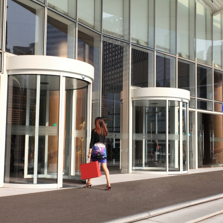 Young female staff through the revolving door photo