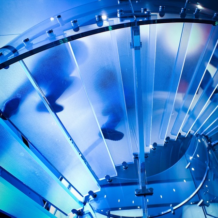 futuristic glass spiral staircase with modern building background in hongkong photo