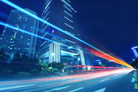 The traffic light trails in the street by modern building Stock Photo