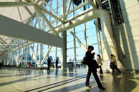 Futuristic Guangzhou Airport interior people walking in motion blur