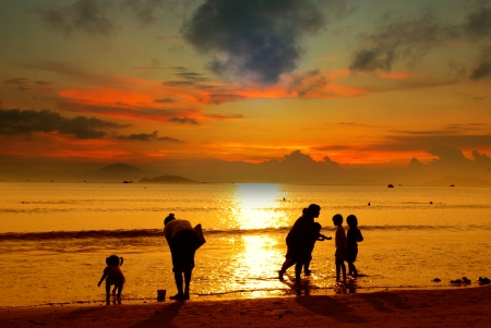 Mother and her kids silhouettes on beach at sunset photo