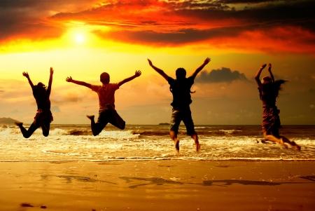 personas saltando: Los jóvenes de la silueta de la playa