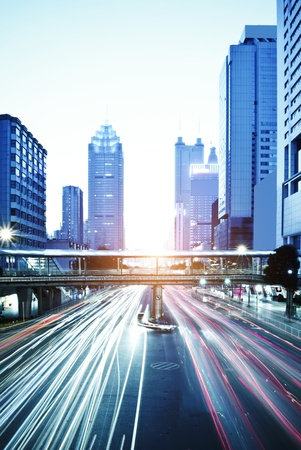 guangdong: moving car with blur light through city at dawn