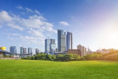 garden city: Parque de la ciudad bajo el cielo azul con el horizonte de la ciudad en el fondo