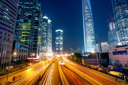 senderos de luz en la calle con el fondo moderno edificio en Shangai, China Foto de archivo