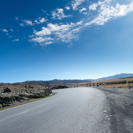 desert road, white clouds and deep blue sky photo