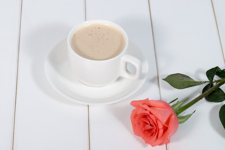 Cups of coffee and pink roses on white background photo
