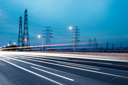 high voltage current: high voltage post.High-voltage tower sky background,besides the highway